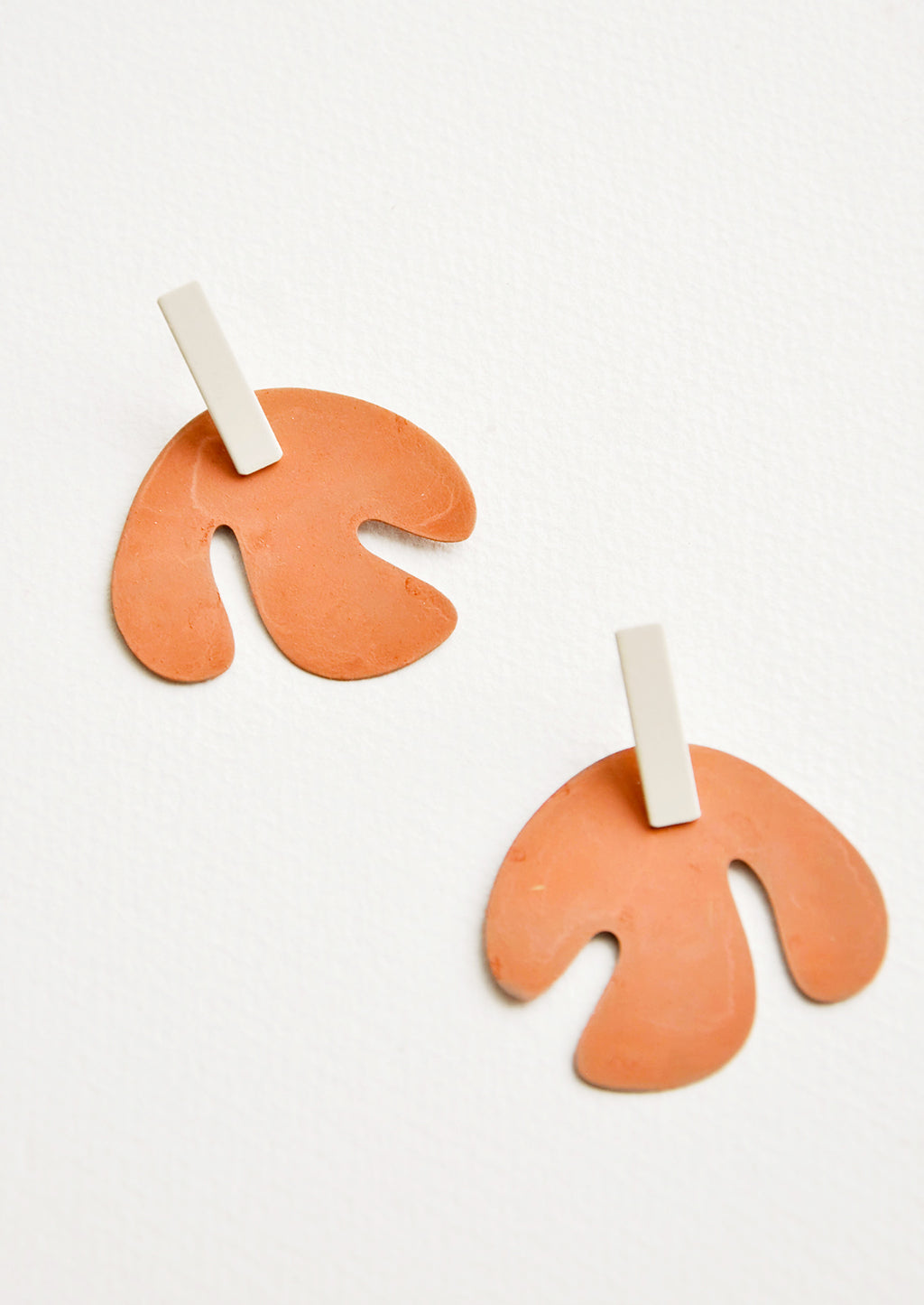 Dark Peach / Cream: Post earrings with orange asymmetric leaf shape hanging from small silver rectangle.
