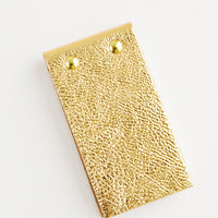 Gold Pebble: Small gold leather notepad with brass grommets.