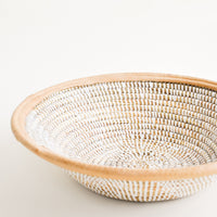 2: A woven seagrass and white plastic bowl with leather trim around top.