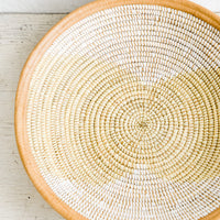 1: A woven seagrass and white plastic bowl with leather trim around top.