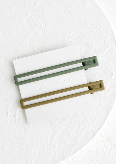 A pair of skinny rectangular hair clips in shades of green.
