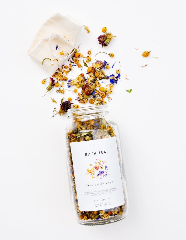 Chamomile Sage: A mix of dried botanicals and a small muslin pouch spill out of a glass jar with a white label.