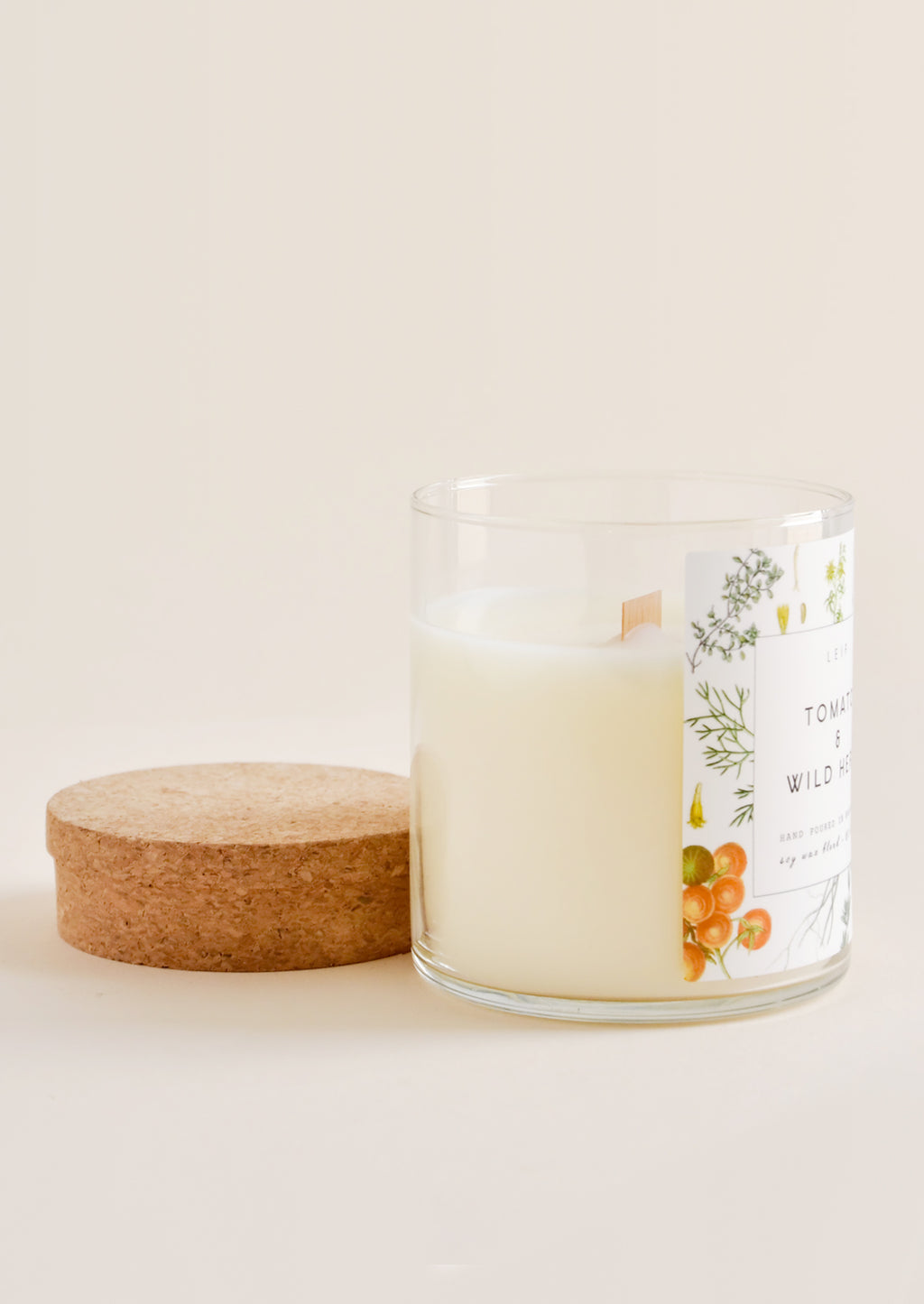 3: A glass candle with botanical label and wooden wick sits next to its cork lid.