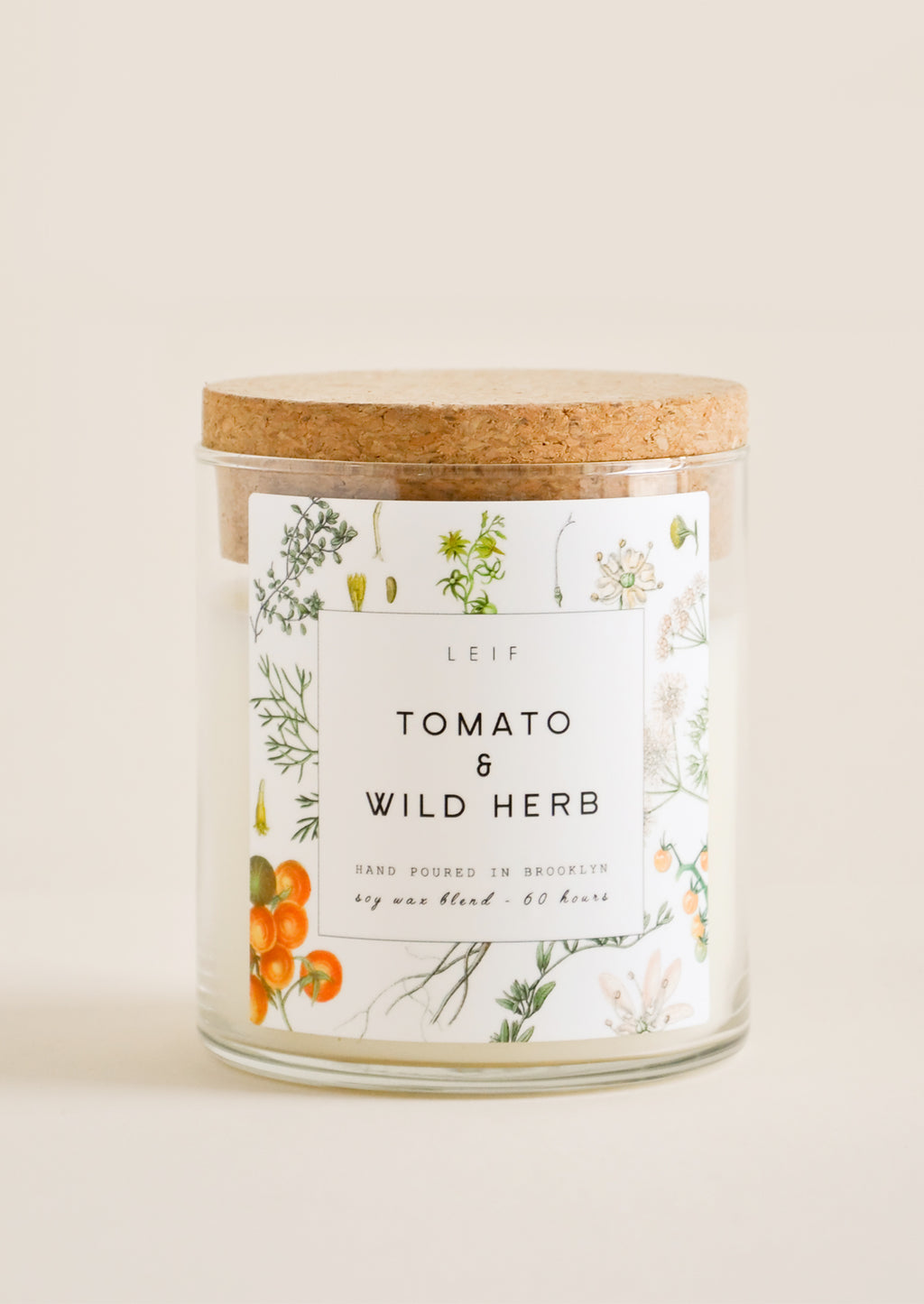 "Tomato & Wild Herb: A glass candle with a cork lid and white botanical printed label reading ""tomato and wild herb."""