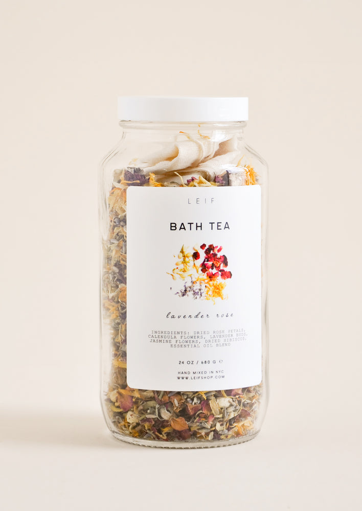 1: A potpourri filled glass jar with a white plastic lid and white label featuring black text and an image of dried flower petals.