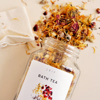 2: A mix of dried botanicals and a small muslin pouch spill out of a glass jar with a white label.