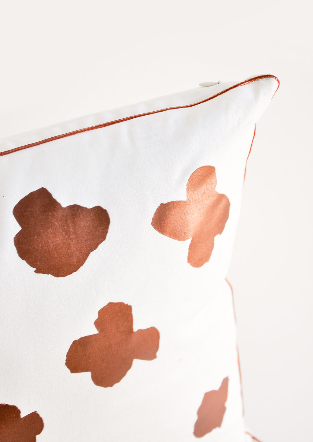 3: Close up of copper trim detail on Square Throw Pillow in White with Copper Abstract Flower Print on Front
