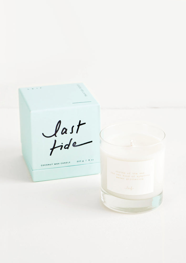 "Last Tide: A glass candle with a white label sits next to a pale blue colored box reading ""last tide"" in black cursive text."
