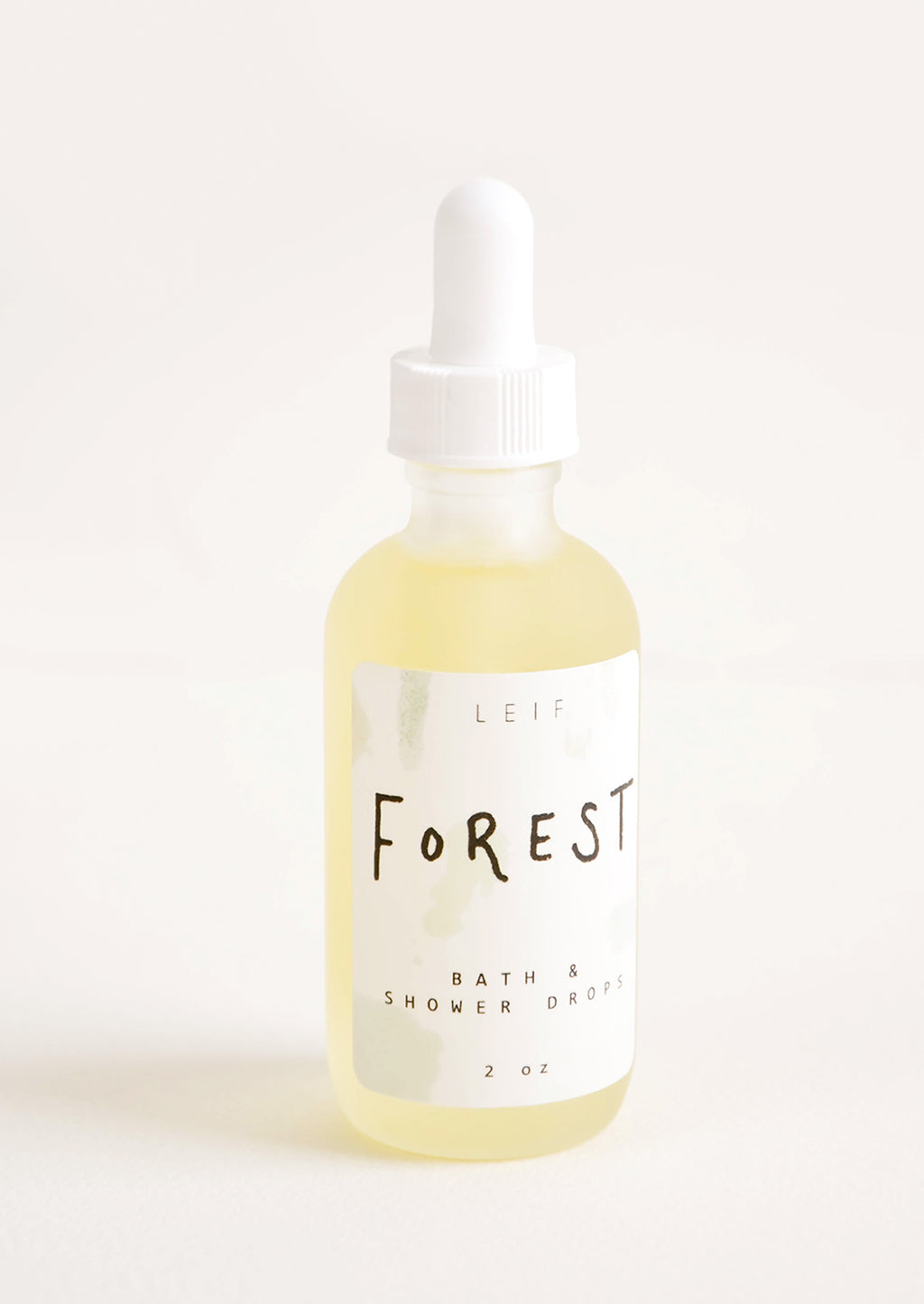 "Forest: A small frosted glass dropper bottle with a white lid and a label reading ""forest"" filled with a pale yellow liquid."