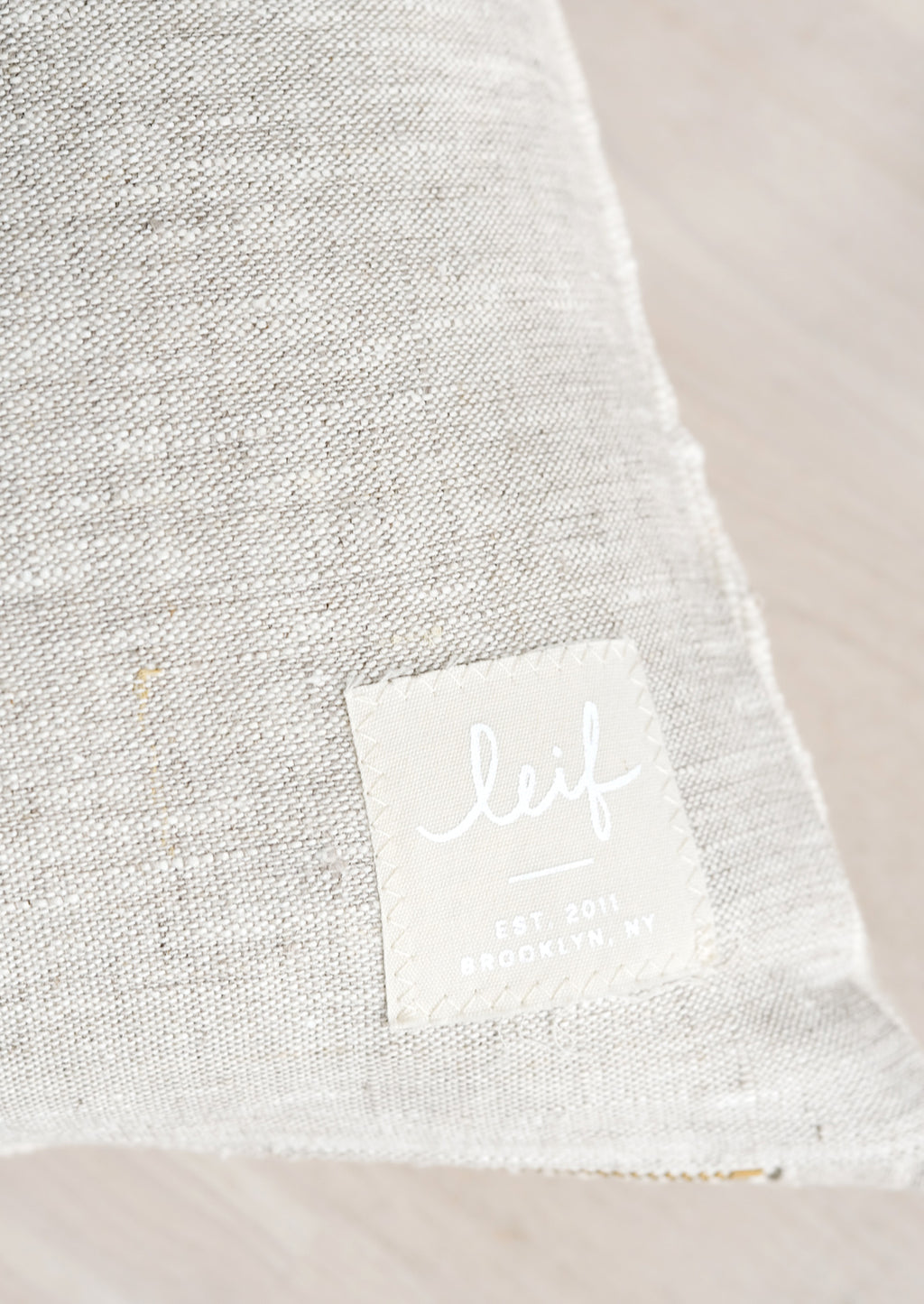 4: Natural linen with hand-stitched square logo patch at bottom corner.