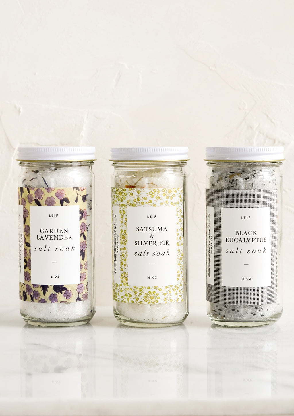 3: Three glass jars with decorative labels containing bath salt soaks.