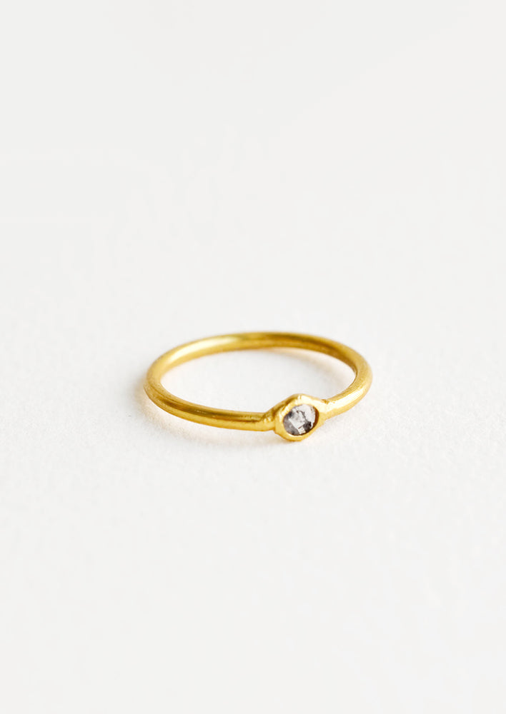 Yellow brass ring with a slim band and a small diamond stone.