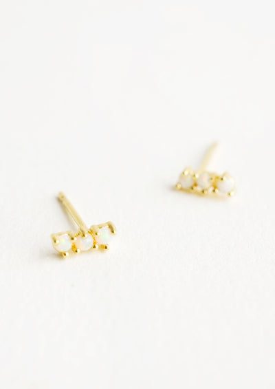 Small gold plated stud earrings with three round white opal stones stacked in a row