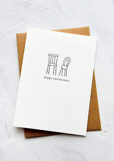 "A letterpress printed greeting card with an image of two chairs side by side, text underneath reads ""happy anniversary""."