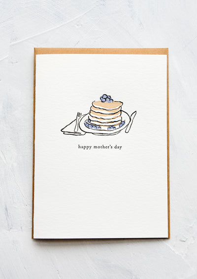 "A letterpress printed greeting card with an image of blueberry pancakes stacked on a plate. Text below image reads ""happy mother's day""."