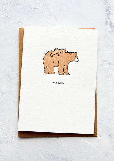 "A letterpress printed greeting card with an image of a baby bear laying on back of larger bear. Text underneath reads ""momma""."