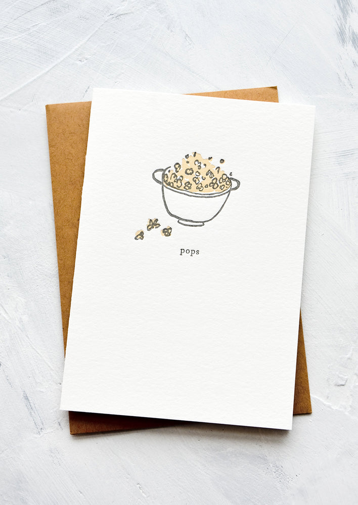 "1: A letterpress printed greeting card with an image of a bowl of popcorn with text below reading ""pops""."