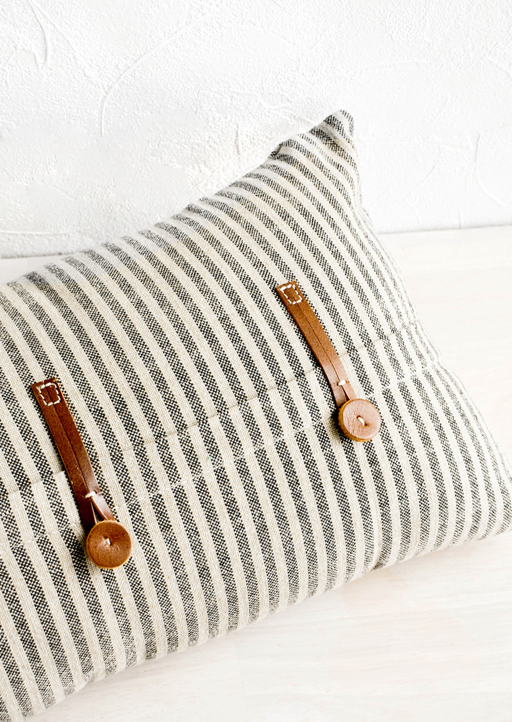 1: Striped cotton pillow in black and beige with decorative leather button detailing