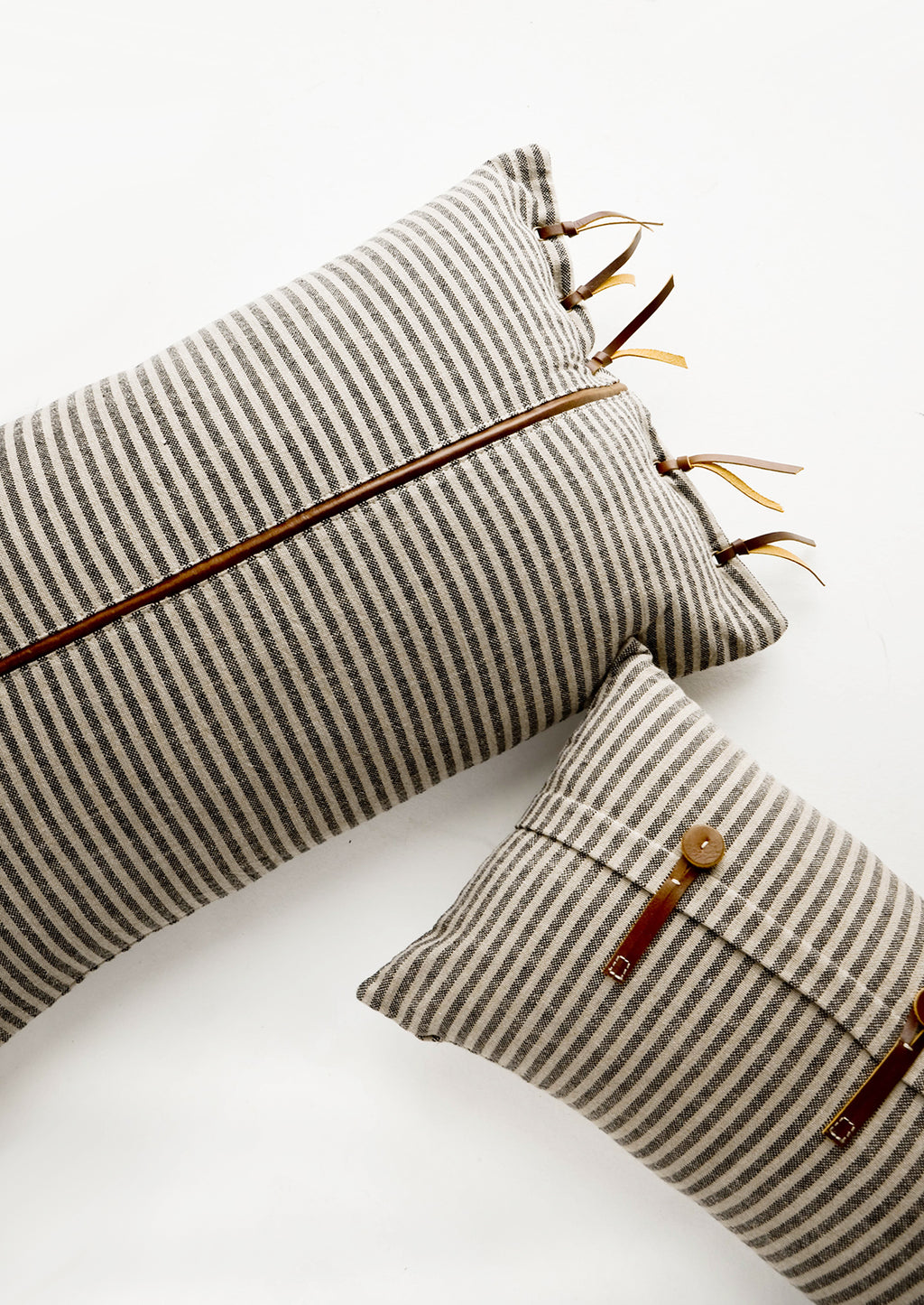 3: Lumbar throw pillows in tan and black striped fabric with brown leather details