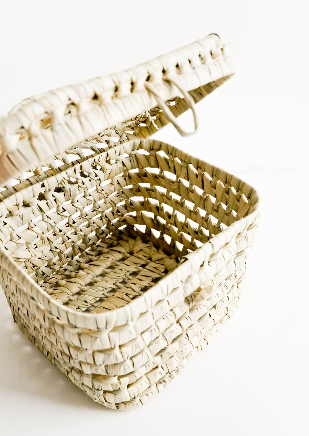 2: The empty interior of a square, lidded basket woven from natural palm leaf.