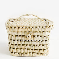 1: A square-shaped, lidded basket made from woven natural palm leaf.