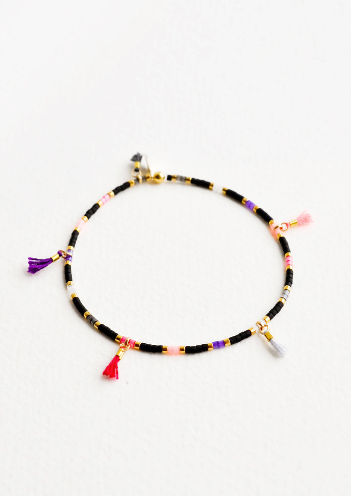 Black Multi: Bracelet featuring black, gold, pink and purple glass beads interspersed with 5 small multicolor string tassels on an elastic cord.