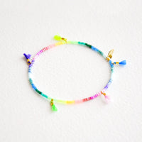Rainbow Gradient: Bracelet featuring multicolor neon rainbow glass beads interspersed with 5 small multicolor string tassels on an elastic cord.