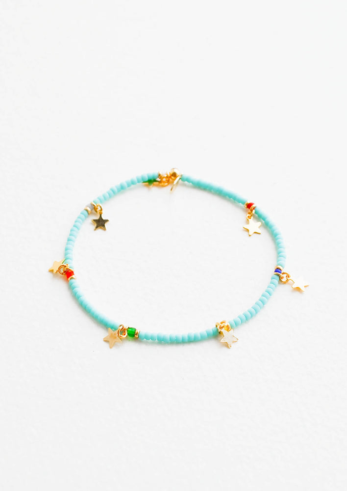 1: Turquoise glass beaded bracelet interspersed with gold star charm and multicolored accent beads, on an elastic cord.