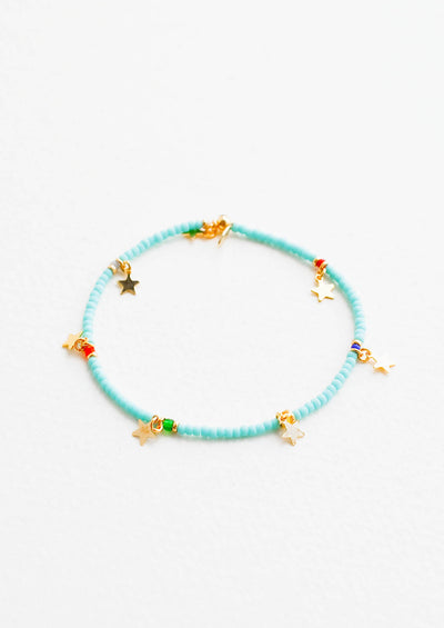 Turquoise glass beaded bracelet interspersed with gold star charm and multicolored accent beads, on an elastic cord.
