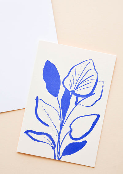 White notecard with cobalt blue lily plant, with white envelope.