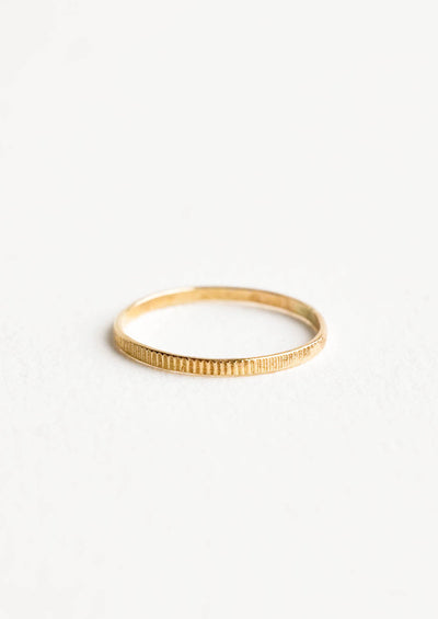 Yellow gold ring with etched decorative markings around the band.