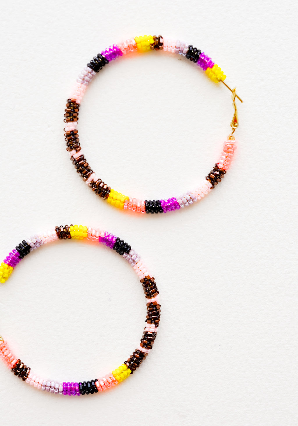 Yellow / Bronze Multi: Hoop earrings with pink, bronze, purple and black glass beads arranged in a circle.