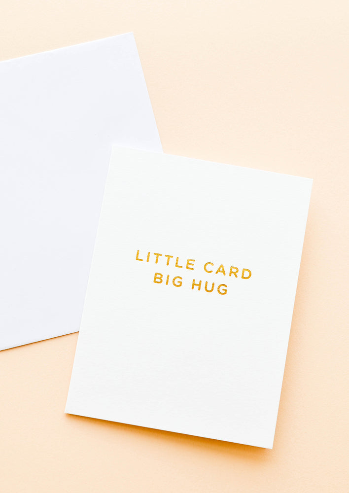 "1: A white greeting card with the words ""little card big hug"" in gold foil."
