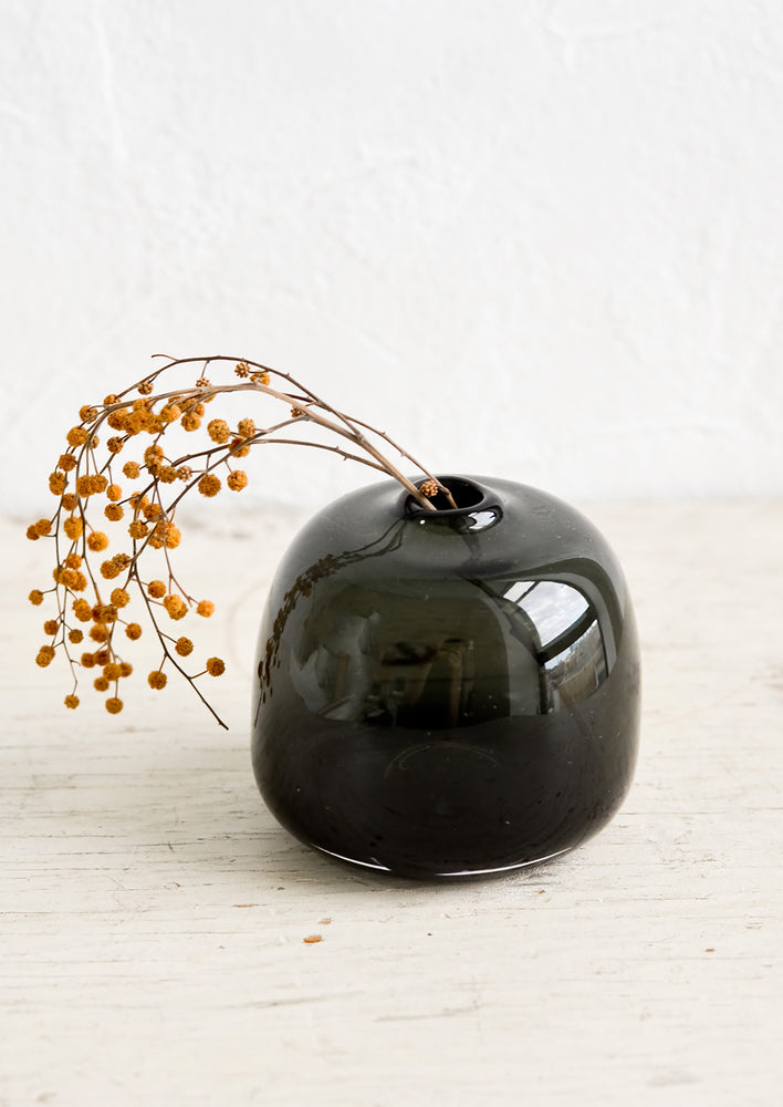 A round, bubble shaped vase in charcoal with dried mimosa.