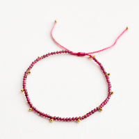 Garnet: A bracelet of small red gemstones and evenly spaced gold beads.