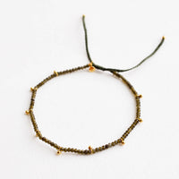 Moss Agate: A bracelet of small green gemstones and evenly spaced gold beads.