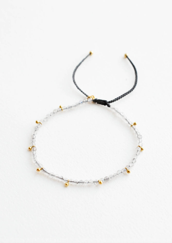 A bracelet of small gray gemstones and evenly spaced gold beads.