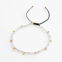 Labradorite: A bracelet of small gray gemstones and evenly spaced gold beads.