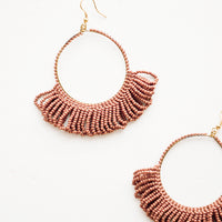 Clay: Dangling hoop earrings featuring clay red beads and accented with hanging beaded, looped fringe.