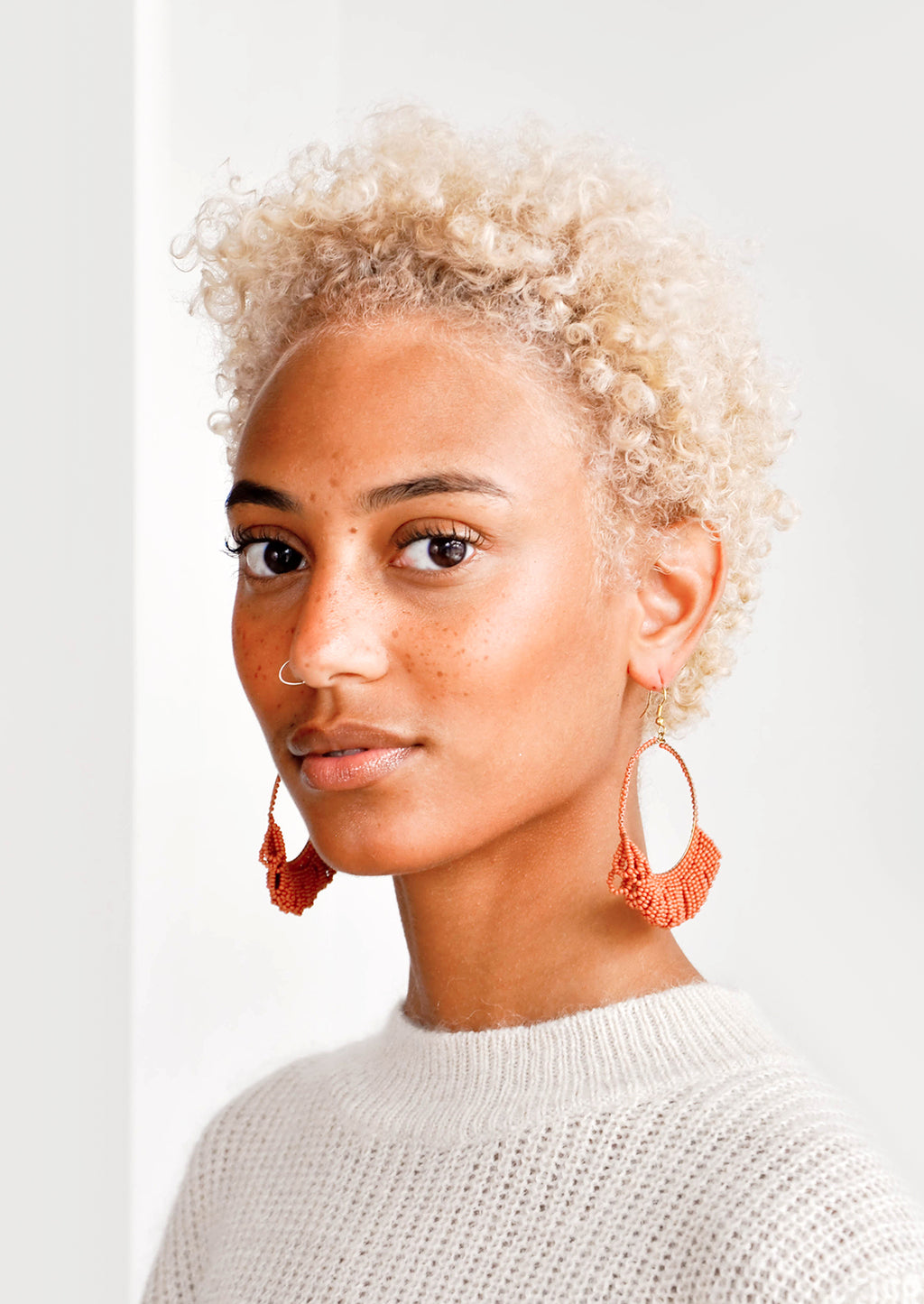 2: Model shot of woman wearing earrings and a white top.