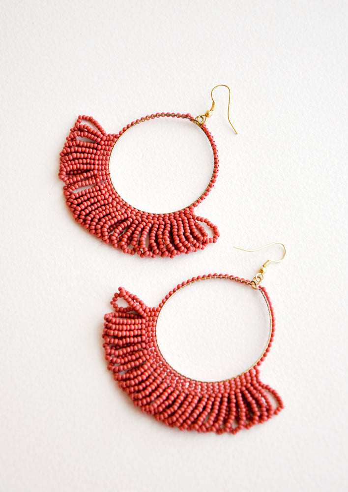 Dangling hoop earrings featuring dark red beads and accented with hanging beaded, looped fringe.