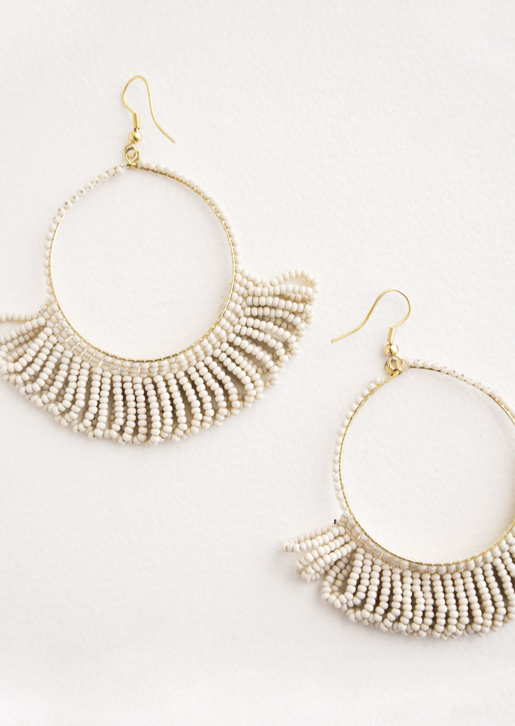 Vanilla: Dangling hoop earrings featuring light grey beads and accented with hanging beaded, looped fringe.