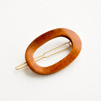 Brown: Oval shaped hair clip made out of brown wood with gold clasp