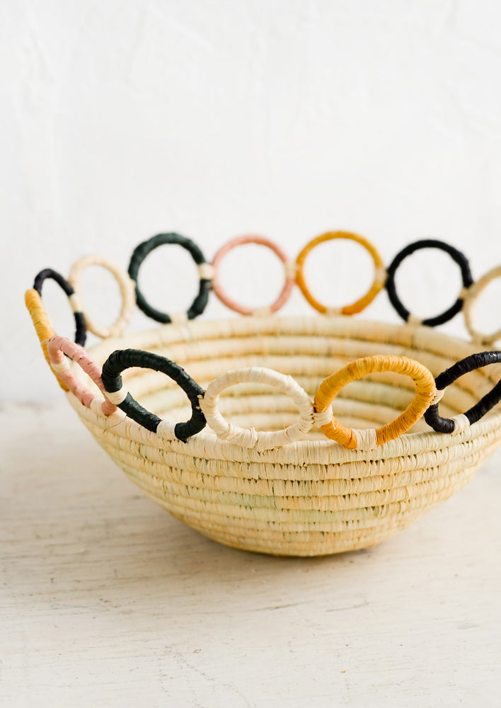 2: A woven raffia bowl in natural with a colorful loopy, circular trim around top.