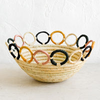Standard / Natural Multi: A woven raffia bowl in natural with a colorful loopy, circular trim around top.
