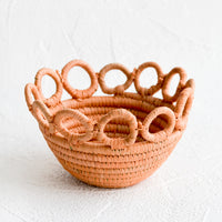 Mini / Dusty Peach: A woven raffia bowl in peach with loopy, circular trim around top.
