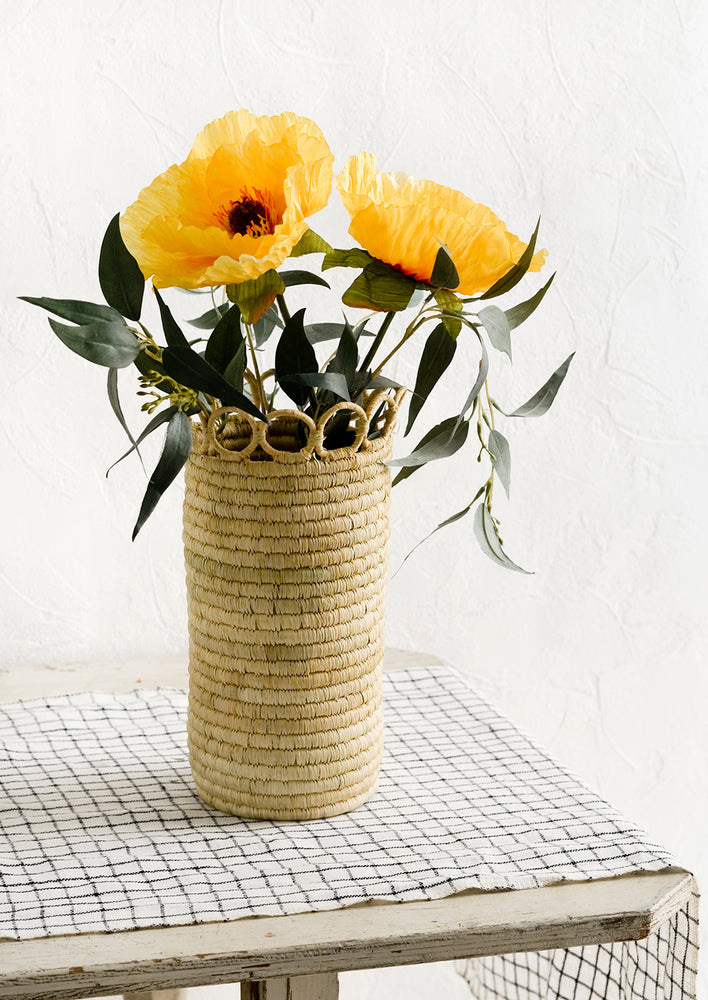 2: A cylindrical raffia vase on a linen-clad table with eucalyptus and poppies.