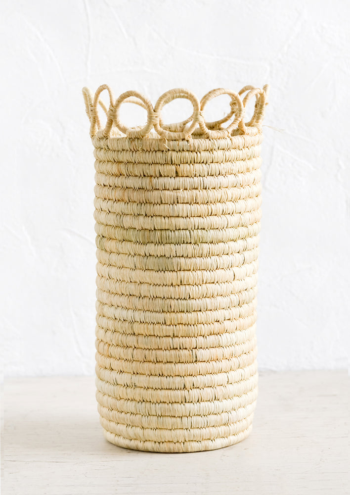 1: A tall, cylindrical vase in natural raffia with open circle trim along top.