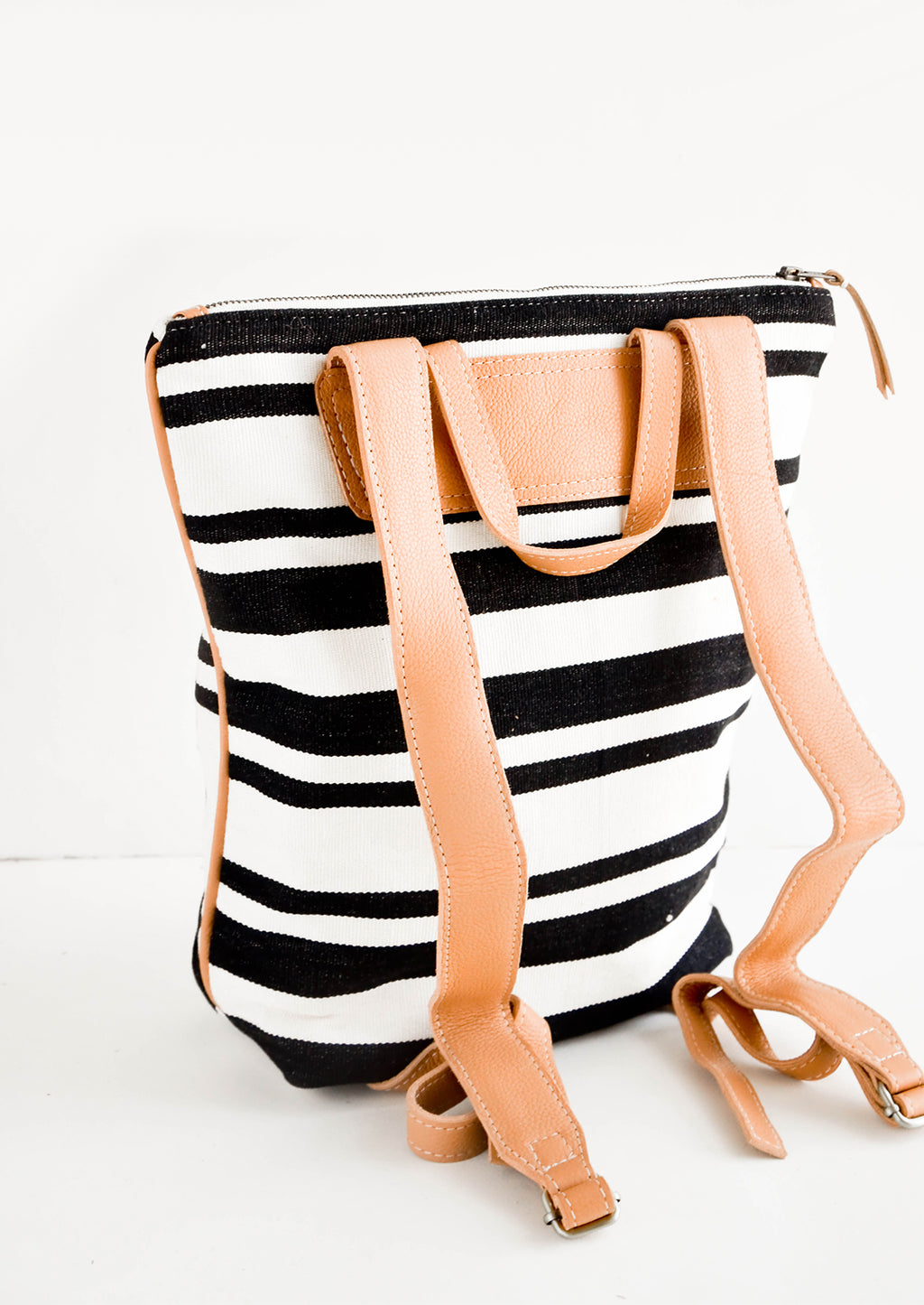 3: Tanned leather straps on the back of black & white striped canvas backpack