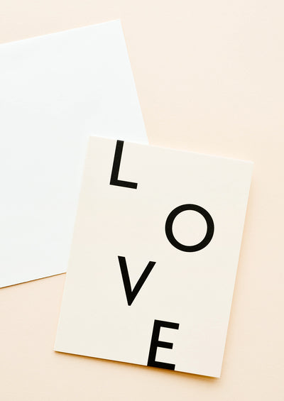 A white envelope and a peachy tan greeting card with the letters L, O, V, and E in black uppercase font.